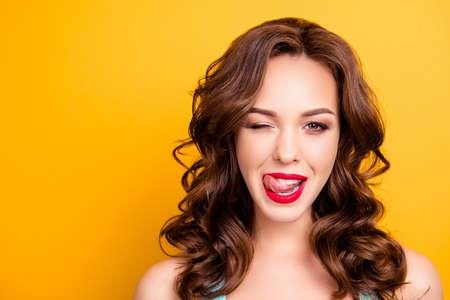 Porträt des reizenden Mädchens mit der modernen Frisur, die Oberlippe mit Zunge heraus zwinkert, die mit einem Auge zwinkert, die Kamera lokalisiert auf gelbem Hintergrund mit Copyspace betrachtet