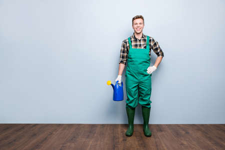 Full-length portrait of glad friendly cheerful satisfied experienced joyful gardener holding watering pot in hand wearing casual checkered shirt isolated on gray background copy-space