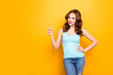 Portrait of charming slim girl pointing forefinger showing copyspace empty place looking at camera holding hand on waist isolated on yellow background, advertisement concept