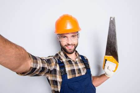 Portrait of handsome cheerful master in overall, shirt, hardhat, uniform shooting selfie on front camera, showing saw in arm, having leisure fun, isolated on grey background Stock Photo