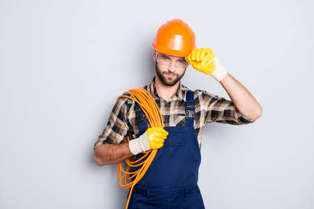 Portrait of virile harsh electrician with bristle in overall, shirt, having rolled cable on shoulder, holding hand on hardhat, standing over grey background