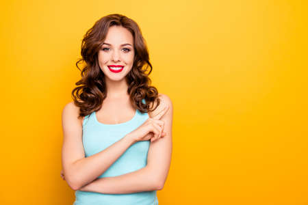 Portrait of good charming girl with beaming smile pointing forefinger showing copy-sapce empty place looking at camera isolated on yellow background, advertisement concept