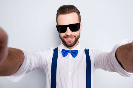 Self portrait of cool famous singer wearing bow, shirt, suspenders shooting selfie on front camera with two hands isolated on grey background Stock Photo