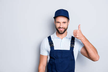 Portrait of cheerful positive deliver in blue uniform with stubble showing thumb up with finger looking at camera isolated on grey background Stok Fotoğraf