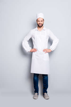 Full size body portrait of attractive handsome butcher isolated over grey background, wearing white shirt, apron, jeans, sneakers, holding arms on waist