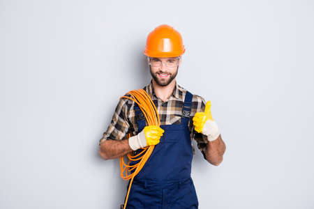 Portrait of handsome joyful electrician in hardhat, overall, shirt with bristle, holding rolled wires on shoulder, showing thumb up recommend approve sign over grey background Stockfoto