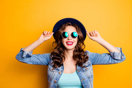 Portrait of toothy cheerful tourist in perfect good mood holding hat on head with hands having beaming smile fashionable look isolated on yellow background. Travel tourism concept Stock Photo