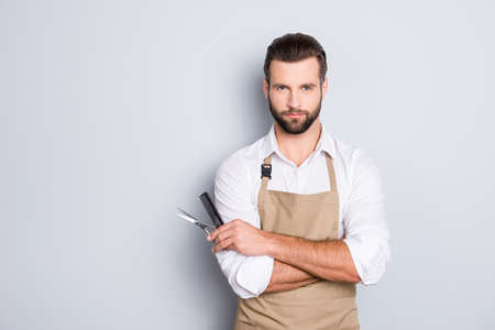 Portrait with copy space, empty place of virile harsh barber having his arms crossed, holding equipments in hand, looking at camera, isolated on grey background