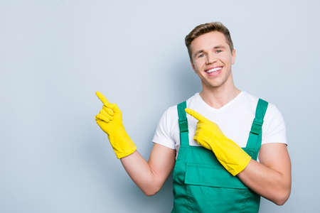 Domestic disinfection people care brushing purity people mug cleanup person concept. Portrait of confident glad friendly guy demonstrating copyspace with forefingers isolated on gray background