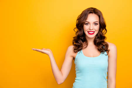 Portrait of charming pretty girl with modern hairdo red lipstick holding copyspace empty place on her palm looking at camera isolated on yellow background