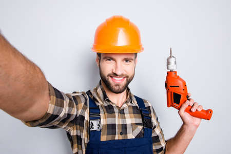 Self portrait of cheerful joyful repairer in protective hard hat shooting selfie on front camera having equipment in hand isolated on grey background. Leisure fun concept
