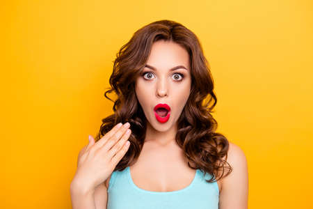 Portrait of shocked impressed woman with unexpected unbelievable reaction gesturing palm looking at camera with wide open eyes mouth isolated on yellow background Stockfoto
