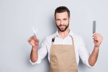 Portrait of cheerful, joyful barber with stubble in shirt having scissors, tools, equipments, comb in hands looking at camera isolated on grey background