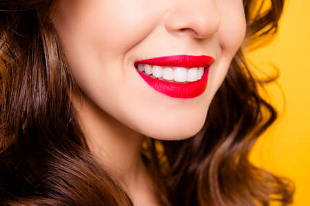 Closeup cropped half face portrait of half-turned lady with beaming smile white healthy teeth having red pomade isolated on yellow background Фото со стока