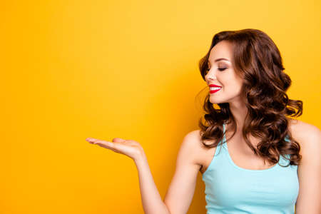 Portrait of positive cheerful girl with modern elegant hairdo red pomade beaming smile holding copy space on her palm looking empty place isolated on yellow background