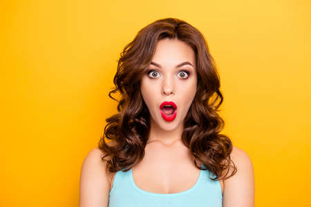 Portrait of shocked astonished girl with modern hairdo having wide open mouth eyes looking at camera isolated on yellow background