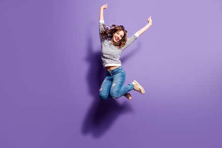 Ritratto di allegra ragazza positiva che salta in aria con i pugni alzati guardando la telecamera isolata su sfondo viola. La vita persone concetto di energia