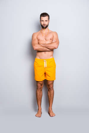 Full size body portrait of muscular athletic man having whistle in lips and crossed arms isolated on grey background