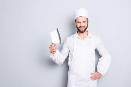 Retrato de carnicero guapo alegre positivo con cuchilla en el brazo sosteniendo la mano en la cintura, mirando a cámara, aislado sobre fondo gris