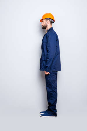 Full size fullbody snap  with legs, profile portrait of calm handsome repairer in blue uniform, isolated on grey background Фото со стока