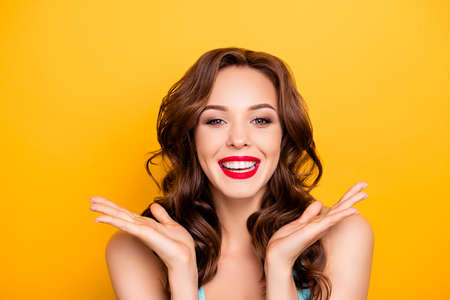 Portrait of cheerful positive girl with modern hairdo laughing gesturing with hands looking at camera enjoying daydream isolated on yellow background