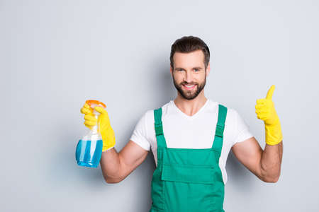 Portrait of cheerful joyful cleaner in uniform overall with stubble holding equipment in hand showing thumbup yes done recommend sign with finger isolated on grey background