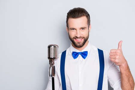 Portrait of attractive handsome singer with bristle wearing bow suspenders shirt showing thumb up, yes, done sign isolated on grey background