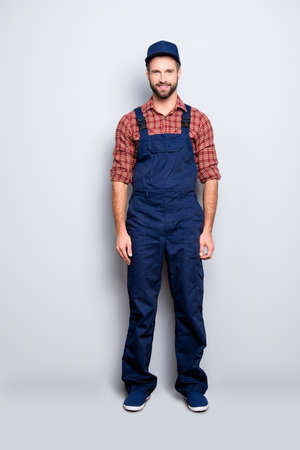 Full body size portrait of attractive positive bearded mechanic with stubble in blue overall shirt cap looking at camera, isolated over grey background