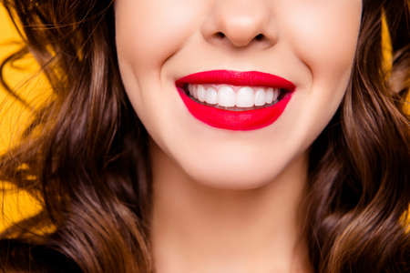 Close up half face portrait of toothy woman with beaming  smile red lips white straight healthy teeth isolated on yellow background advertisement concept