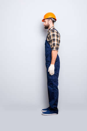 Full size fullbody snap, profile portrait with legs of virile harsh repairer in shirt and overall isolated on grey background