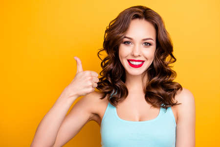 Portrait of positive pretty girl with beaming smile modern hairdo gesturing thumb-up sign like symbol with finger looking at camera isolated on yellow background