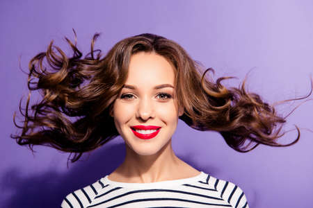 Portrait of pretty sexy girl with flying hair red lipstick white teeth enjoying wind blow looking at camera isolated on violet background. Haircare concept Stock Photo