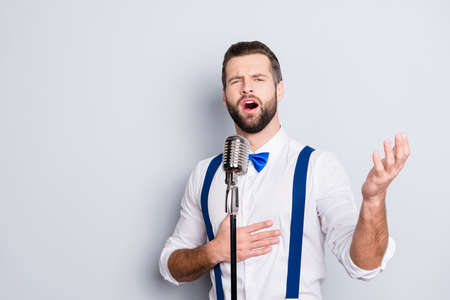 Portrait of talented attractive singer with bristle stubble in elegant classic outfit, singing hit with open mouth in microphone gesture with hand isolated on grey background