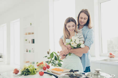 Portrait of dreamy attractive couple in modern white kitchen while preparing meal dinner having ingredients on the table, handsome man making surprise for lover
