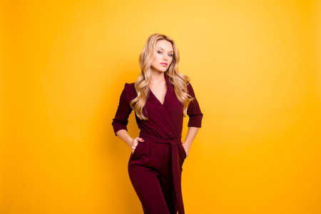 Portrait of stylish stunning lady,  haughty seductive woman holding two hands in pockets looking at camera isolated on yellow background