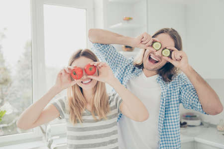 Portrait of positive cheerful couple making glasses closing eyes with tomatos and cucumber enjoying rest weekend together. Mood inspiration dream concept