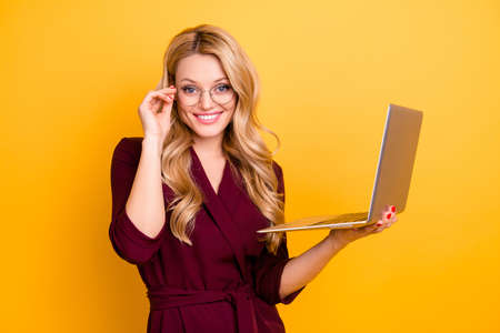 Portrait of positive toothy cheerful woman in formal wear having open laptop in hand holding eyelet of glasses on her face looking at camera isolated on yellow background