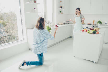 Rear back view of man standing om knee making proposal giving diamond gold ring in casket to shocked surprised lover in modern white kitchen with interior Stock Photo