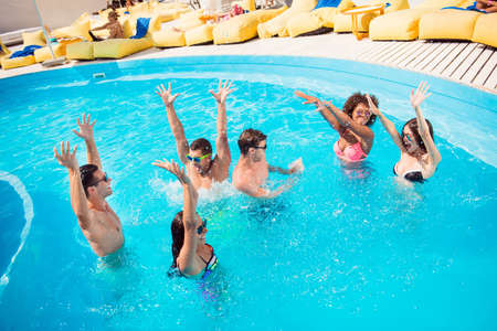 International season cool relationship youth seaside teenagers luxury spa sunshine glasses concept. Six rejoicing funny amusing entertaining glad excited people making splashes in blue clear pool