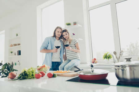 Portrait of dreamy romantic couple drinking alcohol beverage while preparing lunch in modern white kitchen celebrating 8-march. Affection feelings delight harmony concept