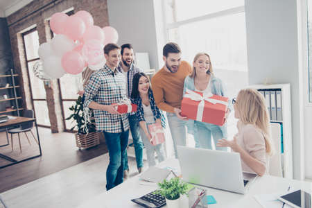 Creative, stylish, attractive, cheerful business people making surprise for their impressed, shocked colleague, manager who sitting in modern office with interior, having cases in package with bow Stockfoto