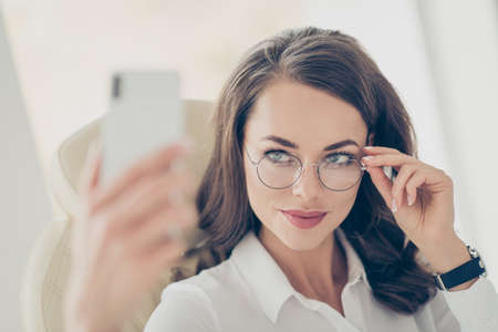 Pretty, charming, trendy, stylish, joyful, cheerful brunette woman with modern hairstyle holding eyelet of glasses on her face with fingers shooting selfie on smart, cell phone in work place, station Stock Photo