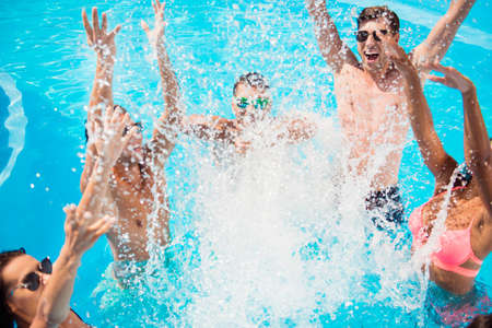 Cropped close up shot of youth going crazy in the pool, splitting water and go insane, huge splashes of blue clear water, guys jump and dabble ladies, they scream and laugh