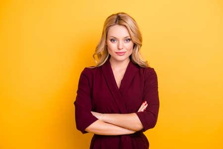Portrait de jolie femme charmante en costume bordeaux ayant les bras croisés en regardant la caméra isolée sur fond jaune Banque d'images