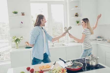 Portrait of cheerful positive couple holding cutlery like sword imagine fencing kidding in modern white kitchen having rest relax leisure enjoying holiday vacation while preparing meal