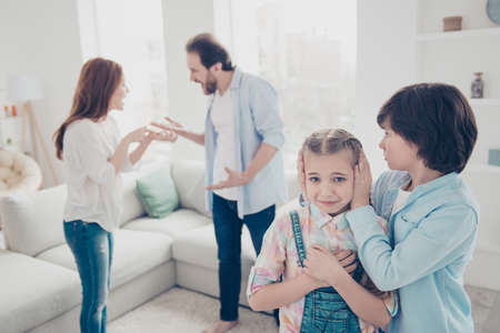 Portrait of nervous annoyed daddy and mom screaming at each other gesturing with hands on blurred background, older brother closing ears of upset misery sister. Crisis disagreement concept