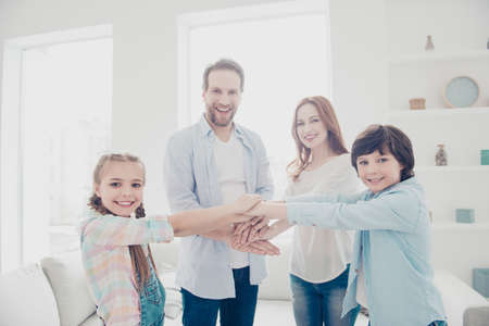 Portrait of cheerful joyful family with two kids standing in white living room putting hands on top of each other making deal looking at camera. Cooperation understanding unity concept Foto de archivo - 104542874