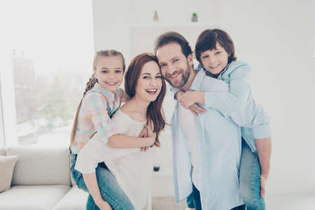 Portrait of lovely beautiful parents in casual outfits carrying on back two kids standing indoor looking at camera. Affection idyllic cuddling care concept Stock Photo