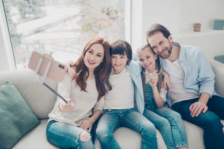 Portrait of friendly bloggers mom dad two kids sitting on sofa using smart phone gadget monopod shooting selfie in front camera gesturing v-sign peace symbol with two fingers having video-call Stock Photo