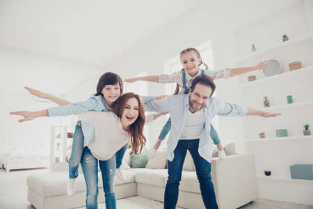 Low angle bottom view of creative joyful family, parents holding on back in piggyback style two kids open hands to the side making airplane in modern white room. Aspiration imagination concept